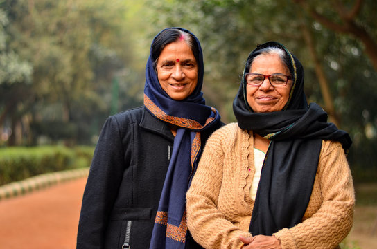 Two senior Indian women friends sisters women standing in a park wearing sweater, shawl, stole and coats during winters in New Delhi, India