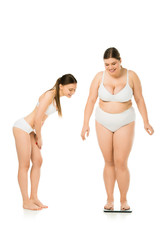 smiling slim woman in underwear looking at happy overweight woman on scales isolated on white, body positivity concept
