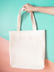 Blank white tote bag canvas fabric with handle mock up design. Close up of woman hand holding eco or reusable shopping bag on green orange background. No plastic bag and ecology concept. Copy space.