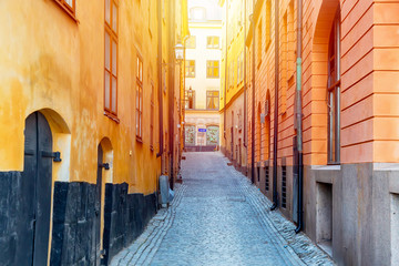 The narrow cobblestone street with yellow medieval houses of Gamla Stan historic old center of Stockholm at summer sunny day. Wall mural