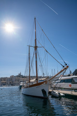 beautiful big wooden sailing ship with two masts morred in the marina of Marseille Vieux Port with Notre Dame de la Garde in Background