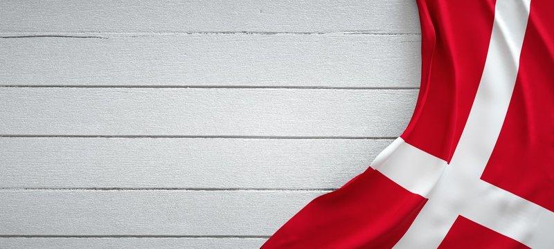 Denmark flag, on top of white wood. Wrinkled fabric.