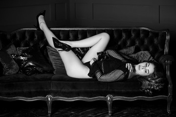 Sexy redhead woman in dark lace lingerie at vintage interior. Lady with fashionable figure, full hips, nice legs
