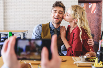 selective focus of beautiful and kissing couple posing for photo at cafe