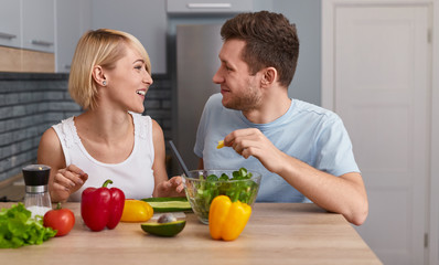 Happy man and woman preparing vegetable salad