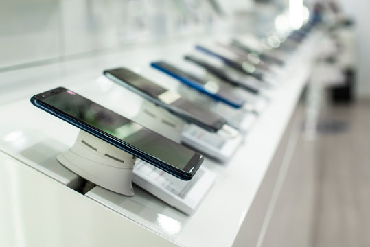 Smartphones on shelf in the store. Concept for communications and technology.