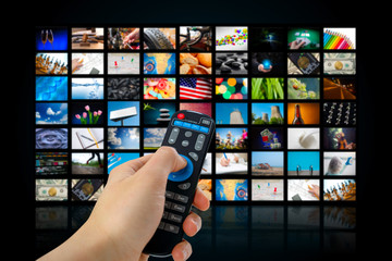 TV screen with lot of pictures and hands of man with remote control .