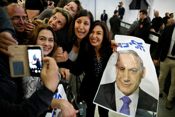 Israel's Minister of Culture and Sport Miri Regev and supporters of the Likud Party hold a photo of Israeli Prime Minister Benjamin Netanyahu at the launch of Likud party's election campaign in Ramat Gan