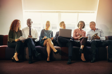 Smiling group of diverse businesspeople sitting on an office sof