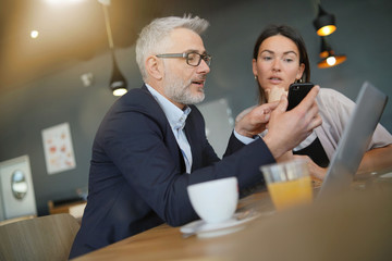 Salesman showing manager proposal on cellphone during meeting