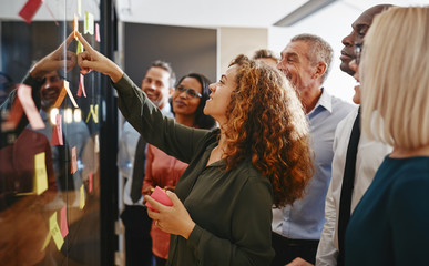 Diverse businesspeople brainstorming with sticky notes in an off