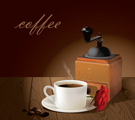 A cup of coffee and coffee grinder.