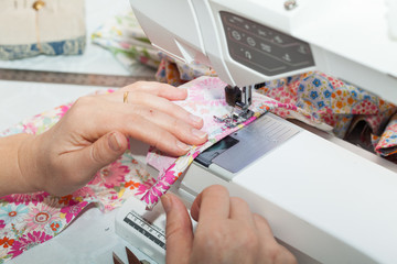 Seamstress hands at work, threads and needles