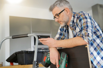 Mature man checking phone whilst fixing shelf in modern kitchen