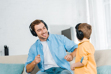 happy father with preschooler son in headphones listening music at home