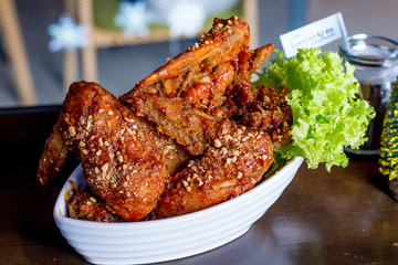 Yangnyean Chicken Wing coated with crushed nuts and lettuce on the side