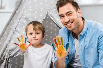 happy father and son looking at camera and showing painted hands at home