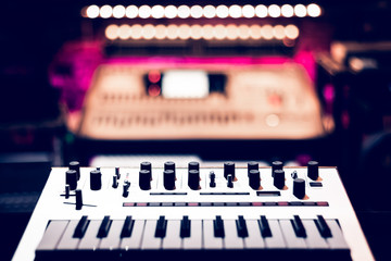 keyboard synthesizer in recording studio, shallow dept of field. music background