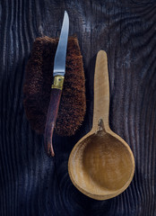 Wooden cup next to knife on a brush