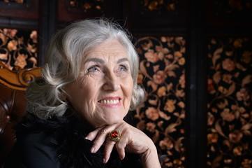 Senior smiling woman in boa posing at home