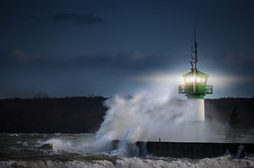 lighthouse during storm in splashing spray  at night on the Baltic Sea, Travemuende in the Luebeck bay, copy space