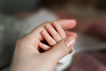 Close up baby's hand put on mom's hand. Mom nursing baby. mom and baby boy relax at home. Nursery interior. Mother breast feeding baby. Family at home. Mom's love. selected focus