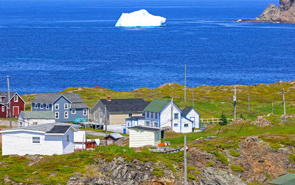 Iceberg in Harbour. Twillingate, Newfoundland, Canada. Maritime homes along the rugged cove shoreline in this coastal community,