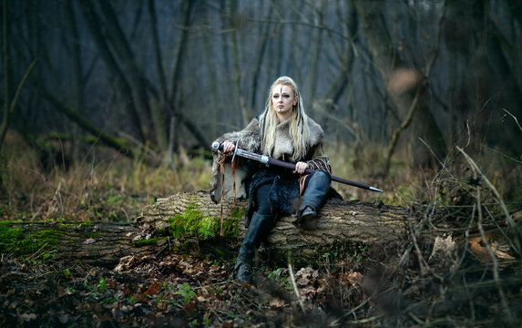 Mad furious viking woman warrior with a sword in her hands, in the woods. Authentic recreation of Norse mythology, myths of the North Germanic peoples. Book Cover