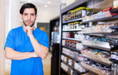 muscular man  standing near shelves with sport nutrition