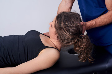 Physiotherapist doing a mobilization neck of female patient. Manual therapy.  Neurological physical examination. Osteopathy, Chiropractic