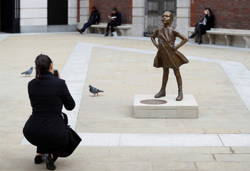 A woman takes a picture of the 'Fearless Girl' statue unveiled by State Street in the financial district of London