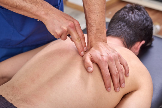 Therapist doing diacutaneous Fibrolysis, of the hooks healing treatment on man's back. Alternative medicine. Chiropractic, osteopathy, manual therapy, acupressure