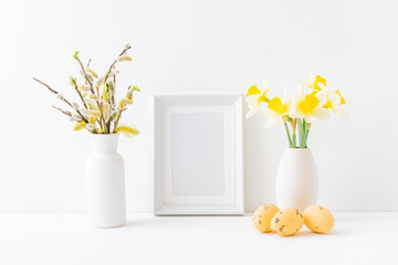 Home interior with easter decor. Mockup with a white frame and yellow daffodils in a vase on a light background