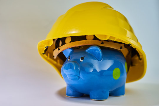Blue piggy bank wearing a yellow construction helmet displaying saving for housing or house and expences for craftsmen