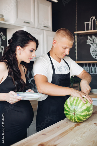 Happy Young Couple Of People Standing At Kitchen And Eating