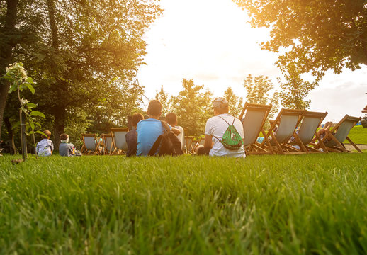 People sit in the park at the summer cinema.