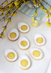 Homemade Easter lemon cookies and forsythia blooming twigs on a light background.
