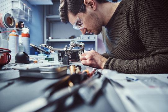 Electronic technician working in the modern repair shop
