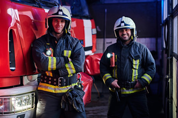Two firemen wearing protective uniform standing next to a fire engine in a garage of a fire department, smiling and looking at a camera