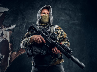 Special forces soldier in military uniform wearing mask and hood holding an assault rifle. Studio photo against a dark textured wall