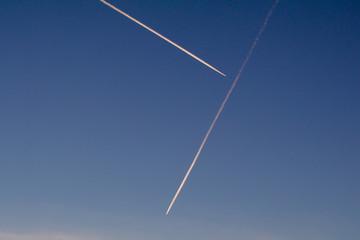 Zwei Flugzeuge am Abendhimmel mit Kondensstreifen im roten Sonnenlicht