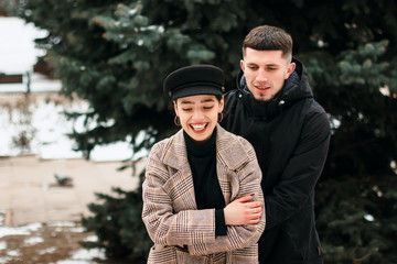 Stunning sensual outdoor portrait of young stylish couple posing in park in winter