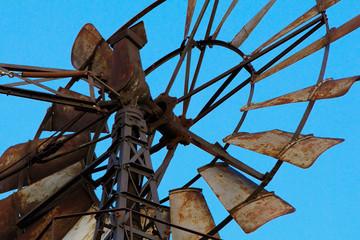 Windrad aus Metall einer Windmühle für eine Wasserpumpe vor einem blauen Himmel