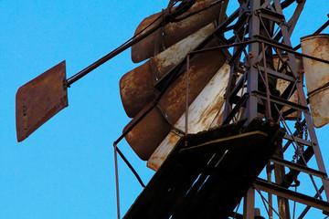 Flügel aus Metall einer Windmühle für eine Wasserpumpe vor einem blauen Himmel