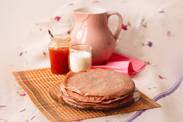 Many Russian-style thin pancakes with crispy crust served with cream and milk.
