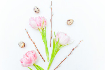 Spring greeting card. Easter eggs cotton willow branch and pink fresh tulip flowers bouquet on rustic white wooden background. Easter concept. Flat lay top view copy space. Spring flowers tulips