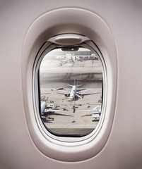 Airplane window view to terminal with airplanes