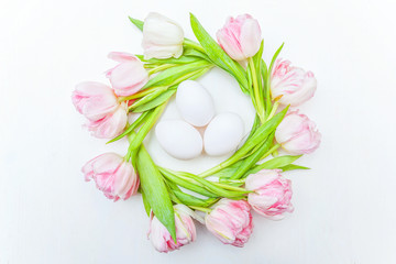 Spring greeting card. Easter eggs in nest and pink fresh tulip flowers bouquet on rustic white wooden background. Easter concept. Flat lay top view copy space. Spring flowers tulips
