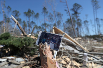 A family photograph sits placed on the remains of a tree outside a destroyed home after two deadly back-to-back tornadoes, in Beauregard, Alabama