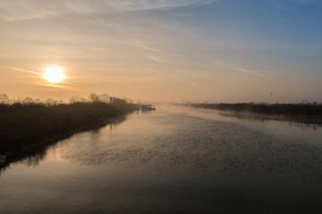 fiume  con argine all'alba con nebbia del primo mattino